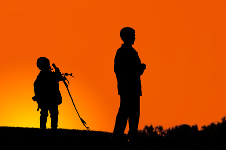 adjusted: Two boys standing on a hill dark silhouette over colorful digitally adjusted orange evening sky Stock Photo