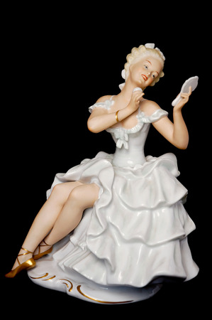 statuette: Ceramic Figure of a Pretty Young Lady Looking at a Mirror Stock Photo
