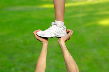 cheerleader: Two strong male hands holding one female foot. Teamwork, support, help, gymnastics, competition concepts. Stock Photo