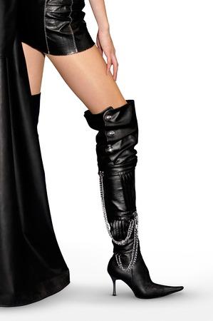 Mujer atractiva en traje de cuero y de cuero negro botas altas de tacón de aguja, aislado silueta sobre fondo rojo con trazado de recorte