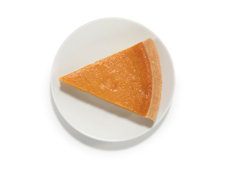 Piece of a pumpkin pie on a saucer isolated on white background with a clipping path