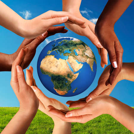 Conceptual peace and cultural diversity symbol of multiracial hands making a circle together around the world the Earth globe on blue sky and green grass background. Stock Photo