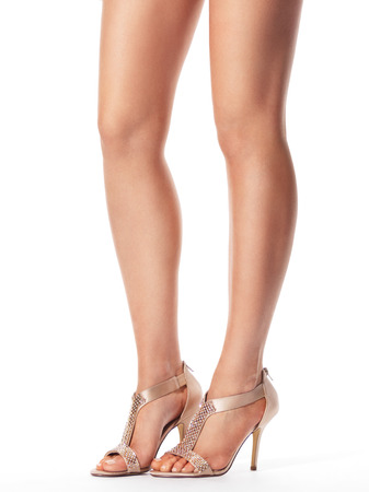 opentoe: Closeup of young woman legs wearing high heel sandals isolated on white background Stock Photo
