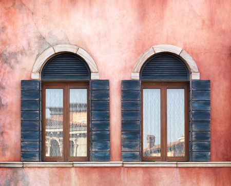 windows: Wall with two old arched windows with shutters, rustic texture