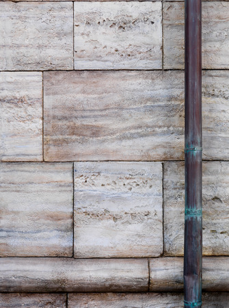 waterspout: Stone wall and old copper downspout background texture