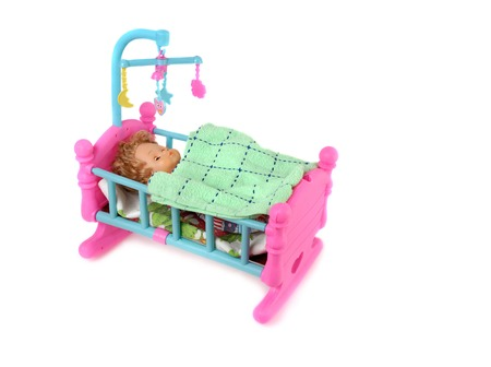 bassinet: Baby doll in toy bed isolated on white background