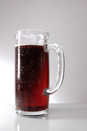 Glass of dark beer over gray background photo