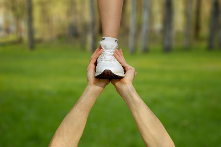 white backing: Two strong male hands holding one female foot. Teamwork, support, help, gymnastics, competition concepts. Stock Photo