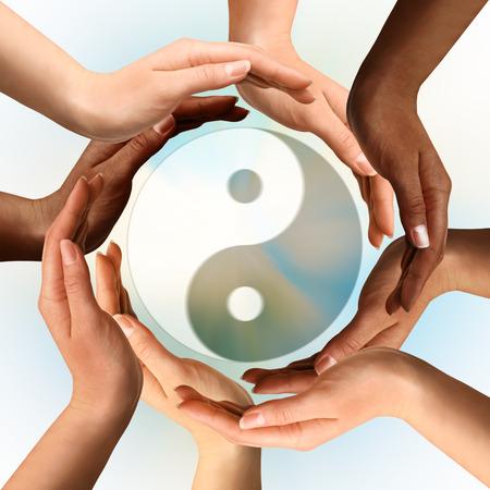 Conceptual yin-yang symbol with multiracial hands surrounding it. Balance, peace, meditation, spirituality concept. photo