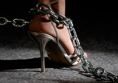 shackles: Sexy woman legs in high heel shoes in chains Stock Photo