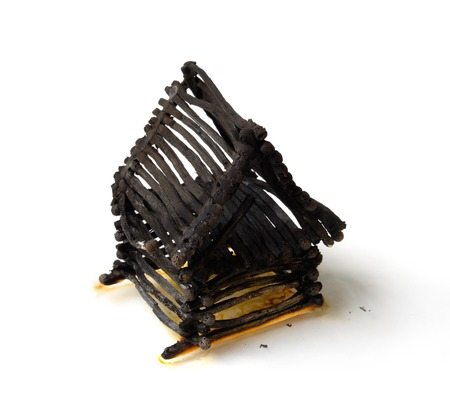 burning house: Ruined house from matches after fire Isolated on white background Emergency property insurance risky investment concept Stock Photo