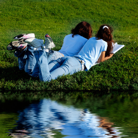 Two girls on grass near water studying in the nature photo