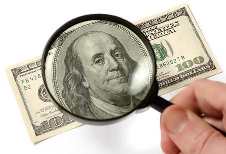 dinero falso: Cientos cuentas de dólar bajo una lupa está siendo inspeccionado Foto conceptual aislado en fondo blanco Foto de archivo