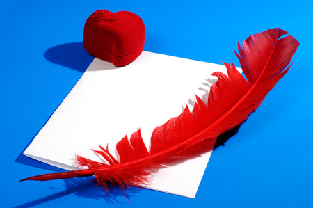 Valentines Day concept. Red heart-shaped jewelry gift box and a red quill on a letter. Conceptual still life isolated on blue background photo