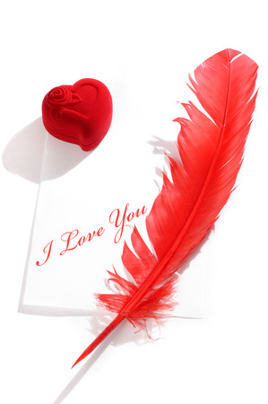 Valentines Day concept. Red heart-shaped jewelry gift box and a red quill on a letter with I love you written on it. Conceptual still life isolated on white background photo