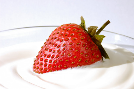 appetizing: Closeup of an appetizing strawberry in cream