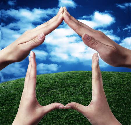 sinergia: Símbolo conceptual a casa hecha de manos de dos personas con la naturaleza en el fondo