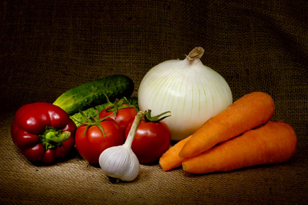 colorful still life: Light-painted colorful vegetable country-style still life with tomatoes, onion, bell pepper, cucumbers, carrots and garlic on sacking fabric background Stock Photo