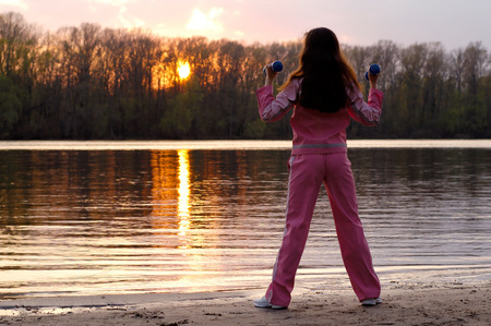 Young woman with weights exercising in the nature in sunset near the river Healthy lifestyle and fitness concept photo