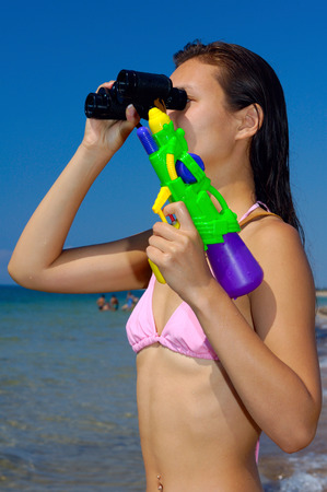 watergun: Woman with water-pistol looking through binocular at the beach