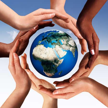 mundo manos: Manos multirraciales que hacen un círculo en torno al mundo del globo de la tierra en el fondo del cielo azul Foto de archivo