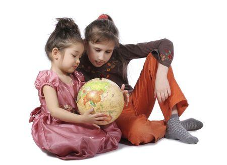 consider: Two girls consider globe on white background