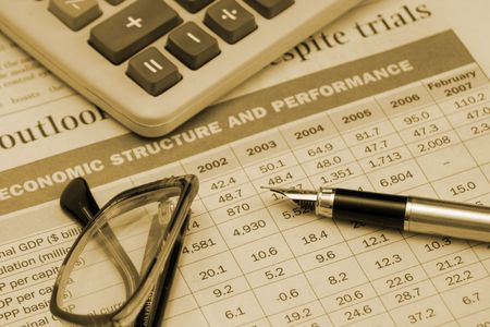 perfomance: pen, calculator and glasses on the table Economic structure and perfomance, made with sepia tones