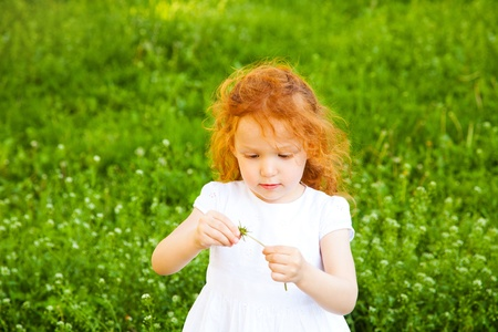 Adorable 3 year old girl playing game with flower, shallow depth of field, focus on foreground photo