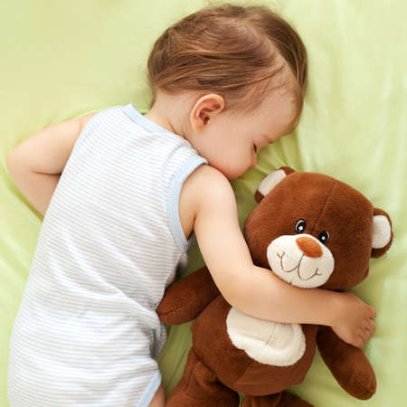 girl lying: Sweet child sleeping with teddy bear