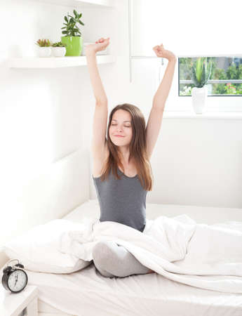 Young woman waking up happily, after a good night sleep photo