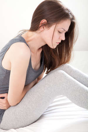 pucker: Young woman in pain sitting on bed, on white background