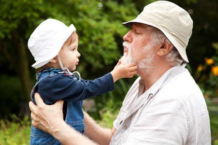 grandchild: Grandchild and grandfather having fun outdoors.