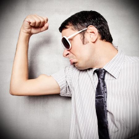 hombre flaco: Empollón joven que muestra sus músculos Foto de archivo