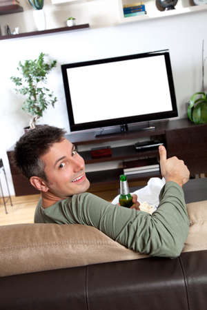 Young man relaxing and enjoying watching TV at home photo