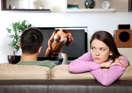 Image of woman getting bored, while her partner watching TVI am the author of image on TV screen Stock Photo - 22158583