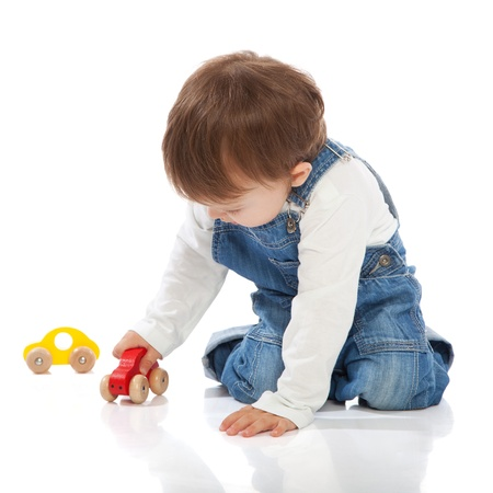 Adorable toddler playing with toy cars, isolated on white photo