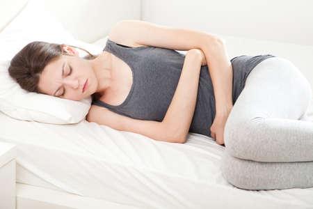 per�odo: Mulher nova na dor deitado na cama Banco de Imagens