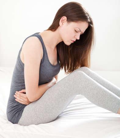 diarrea: Mujer joven en el dolor que se sienta en la cama, en el fondo blanco Foto de archivo