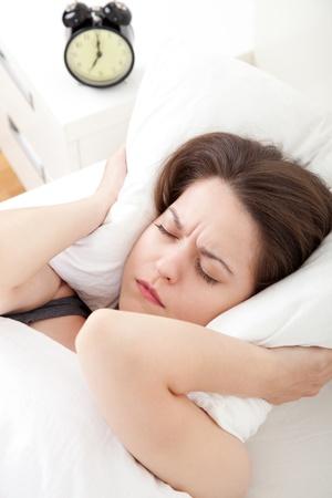levantandose: Mujer joven que tiene problemas con levantarse temprano en la ma�ana, profundidad de campo, se centran en primer plano