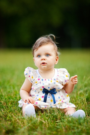 Image of adorable baby girl sitting on grass, shallow depth of field photo