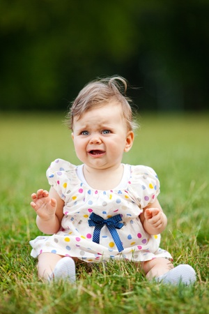 Image of adorable baby girl sitting on grass crying, shallow depth of field photo