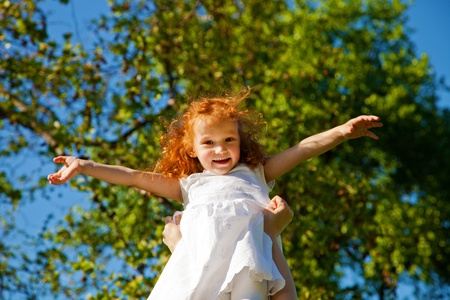 Adorable 3 year old girl playing aeroplane outdoors photo