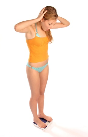 teen girl underwear: Young woman standing on a scale, upset about her weight, on white background