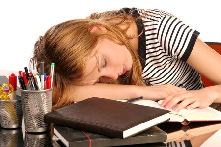 Young woman, tired of studying, sleeping over books photo