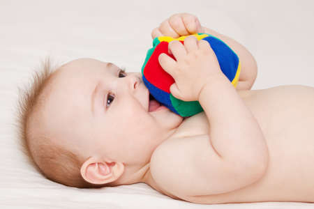 Cute baby lying and playing with a ball photo