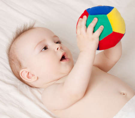 gripping hair: Cute baby lying and holding a ball