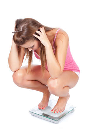 angry teenager: Young woman unhappy with her weight, isolated on white Stock Photo