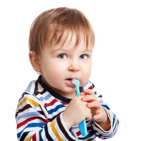 Adorable one year old child learning to brush teeth, isolated on white photo