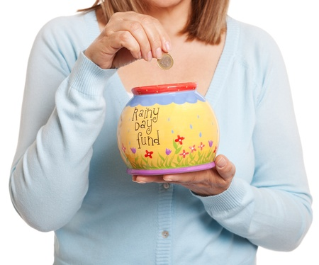 woman holding money: Mature woman putting one Euro coin in her money jar, isolated on white
