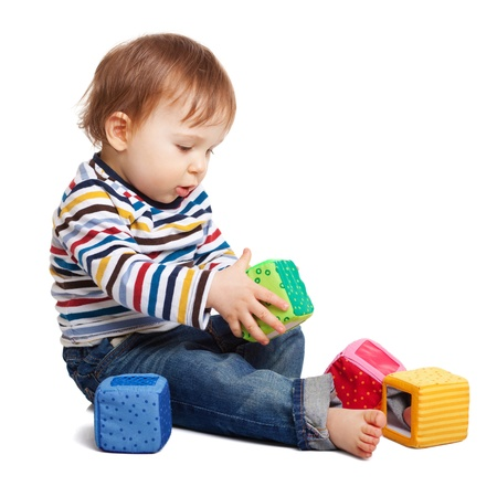 Adorable one year old child playing with toy cubes, isolated on white photo
